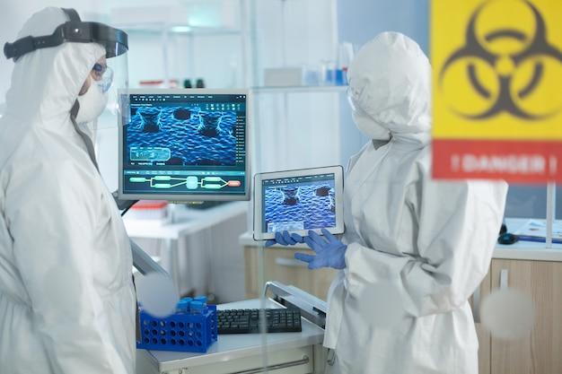 바이러스 개발을 분석하는 보호복을 입은 과학자들의 의료 팀워크