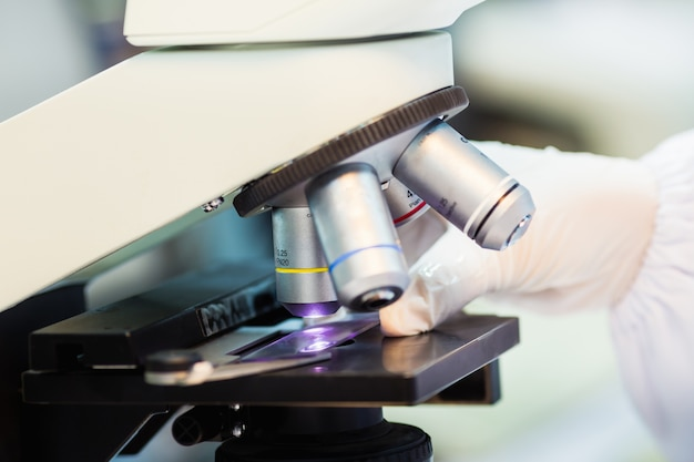 Medical technician using a microscope for checking slide in laboratory