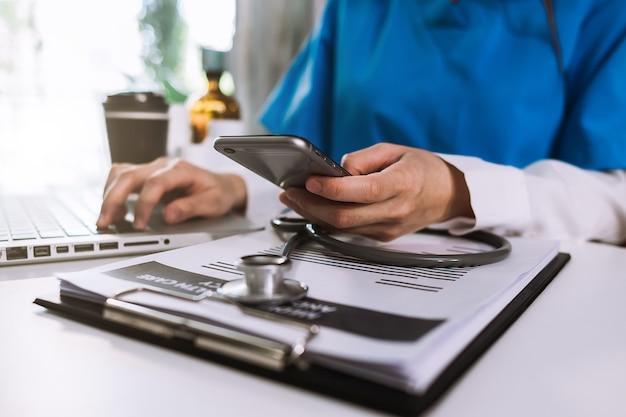 医療技術の概念。朝の光の中で病院の近代的なオフィスで携帯電話と聴診器とデジタルタブレットのラップトップで働く医師