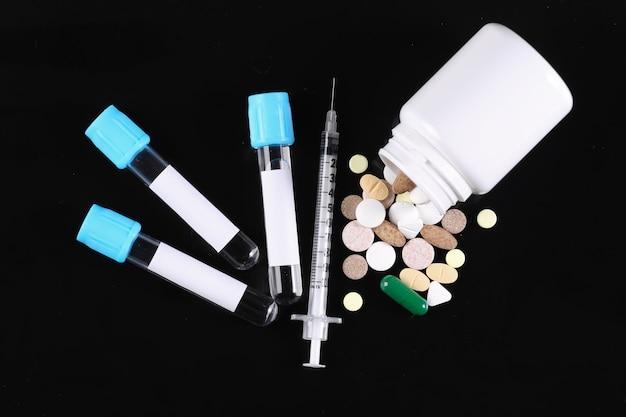 의료 테스트 튜브 및 주사기, 검은 배경에 고립 된 알약