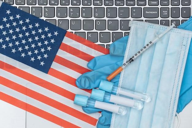 의료 테스트 튜브, 얼굴 마스크, 미국 국기가 달린 노트북 키보드에 주사기가 달린 장갑.