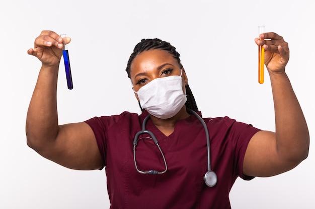 Образцы медицинских пробирок в руке доктора на белой стене.