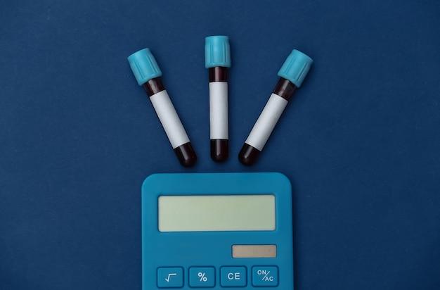 혈액, 고전적인 파란색 배경에 계산기와 의료 테스트 튜브. 평면도
