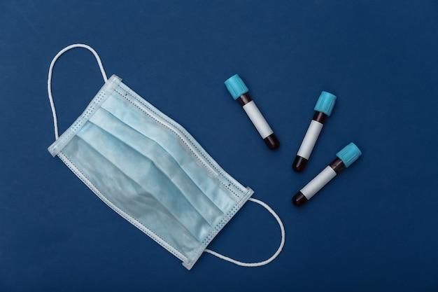 혈액이 있는 의료 테스트 튜브, 고전적인 파란색 배경에 의료 마스크. 평면도