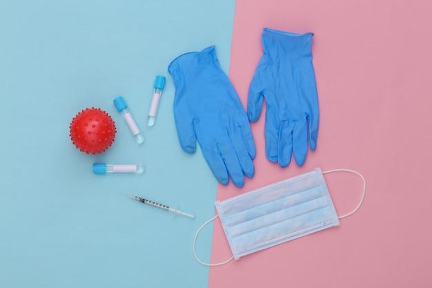 파란색 분홍색 파스텔 배경에 주사기와 얼굴 마스크, 장갑, 바이러스 변형 모델이 있는 의료 테스트 튜브. 백신 접종. 평면도