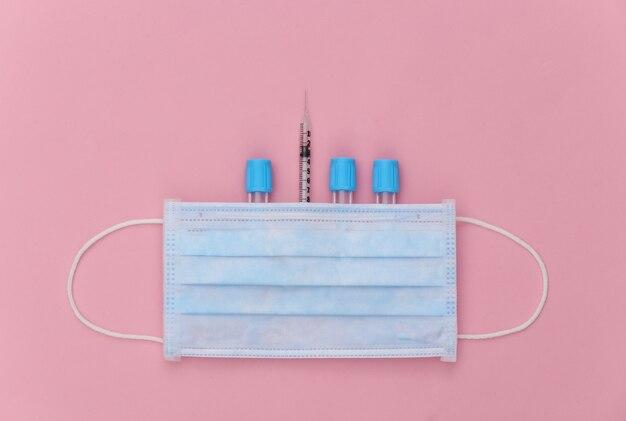 분홍색 파스텔 배경에 주사기와 얼굴 마스크가 있는 의료 테스트 튜브. 평면도