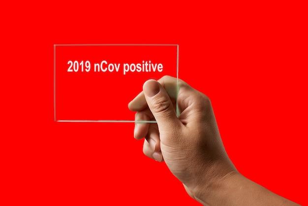 인간의 손으로 의료 테스트 및 2019 ncov에 대한 양성 결과, 빨간색 배경, 복사 공간에 대한 코로나 바이러스 감염. 코로나 바이러스, covid-19 또는 대유행 개념의 발생.