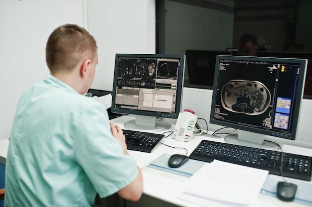 医療テーマ。病院の診断センターにあるmri室の医師で、人間の脳が置かれたコンピューターのモニターの近くに座っています。