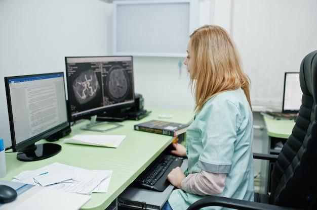医療テーマ。コンピューターのモニターの近くに座っている、病院の診断センターのmriオフィスの医師。