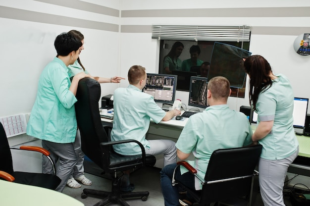 医療テーマ。コンピューター断層撮影装置を備えた観察室。病院の診断センターのmriオフィスで集まる医師のグループ。 x線放射線画像を保持します。