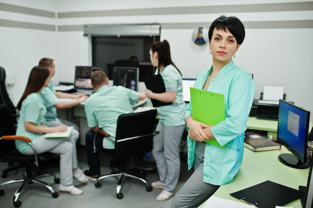 Medical theme .portrait of female doctor with clipboard against group of doctors meeting in the mri office at diagnostic center in hospital.