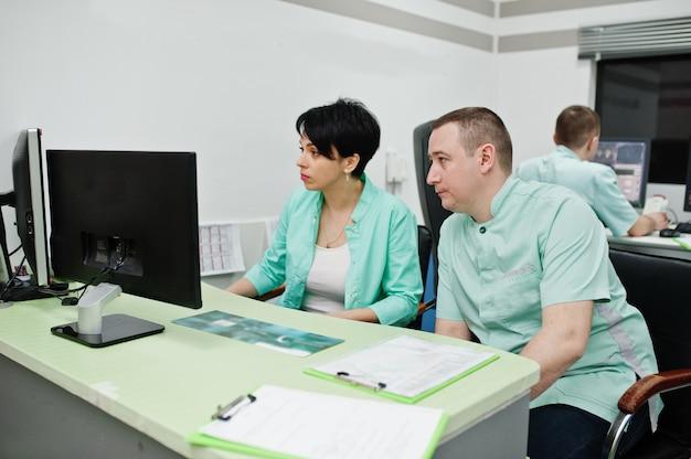 医療テーマ:病院の診断センターのmriオフィスで、コンピューターのモニターの近くに座っている2人の医師が集まります。