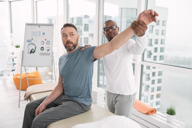 Лечебная терапия. серьезный умный терапевт, держащий руку пациента, выполняя свою работу