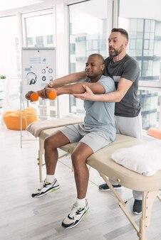 医学療法。彼がダンベルを持ち上げるのを手伝っている間彼の患者の後ろに立っている巧みなハンサムな医者