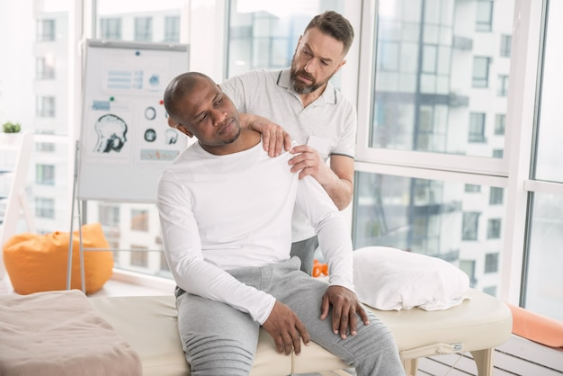 Medical therapy. smart nice man standing behind his patient while checking his shoulder
