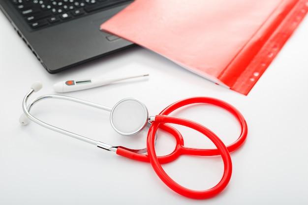 白いテーブルに赤い体温計聴診器。ワークスペースの医師専門機器。ヘルスケア医療コンセプト。医師の任命。コロノウイルスcovid-19予防