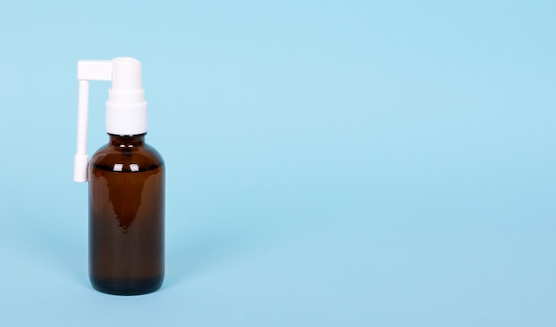 Medical throat spray in glass bottle, isolated on blue background, copy space.