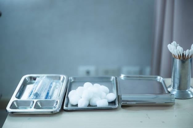 医療器具、スタンレススチールテーブル上の医療キット、車椅子、綿棒、病院用ベッド、注射器、投薬トレイ、ピルカウントトレイ。