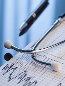 医療器具。テーブルの上の聴診器と心電図。