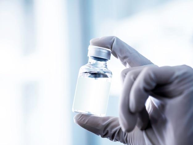白いゴム手袋をした科学者の手に白い空白のラベルが付いた医療用ワクチンバイアル。注射用ワクチンガラス瓶を持っている手の画像をクローズアップ。