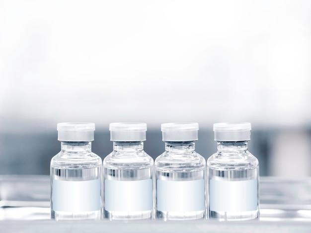 복사 공간이 있는 트레이에 흰색 빈 레이블이 있는 의료 백신 병. 주사용 백신 유리병 4개의 이미지를 닫습니다.