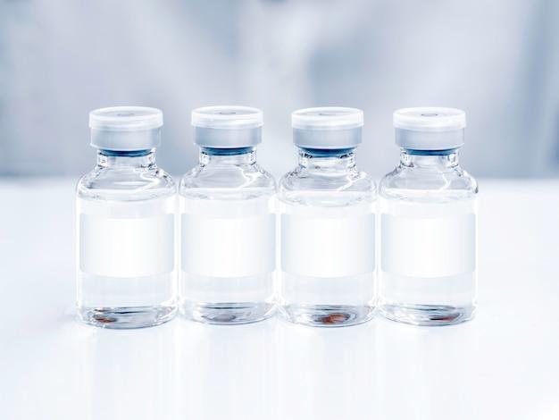흰색 테이블에 흰색 빈 레이블이 있는 의료 백신 병. 주사용 백신 유리병 4개의 이미지를 닫습니다.