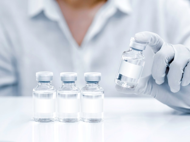 Medical vaccine vials with white blank label in scientist hand with white rubber gloves. close up image of hand holding vaccine glass bottles on white clean table for injection.