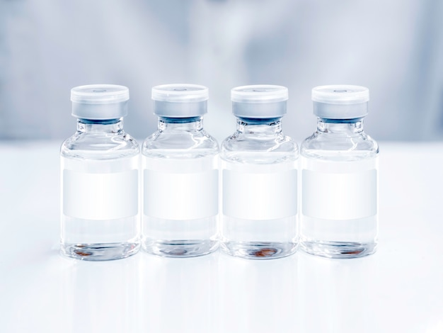 Medical vaccine vials with white blank label on white table. close up image of four vaccine glass bottles for injection.