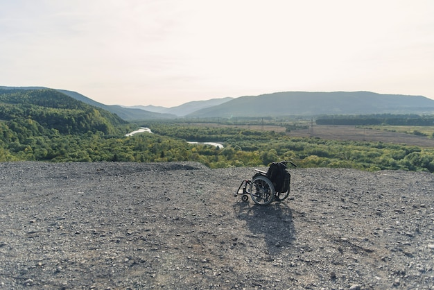 Medical wheelchair in beautiful nature and high mountains. rehabilitation concept.