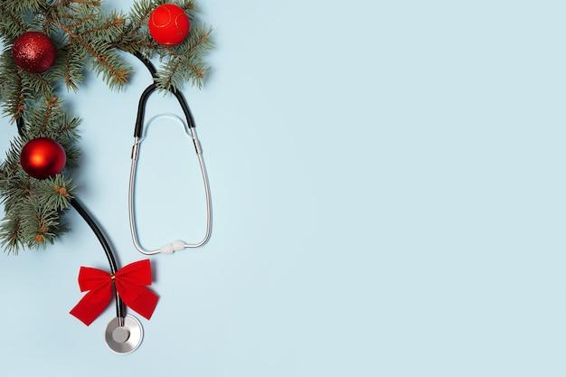 聴診器、ボール、クリスマスツリーと医療の冬の青