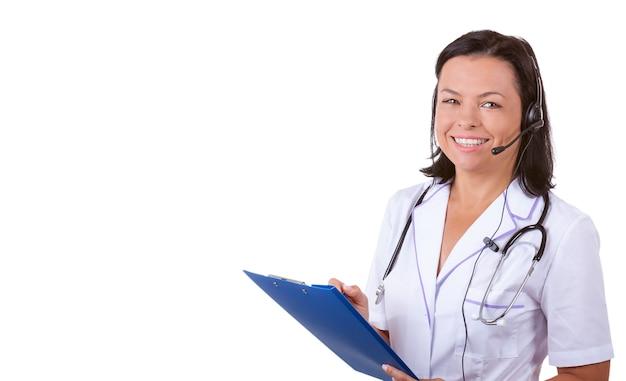 白い背景の上のあなたのデザインのためのコピースペースでクリップボードを保持聴診器とヘッドセットの医療女性医師