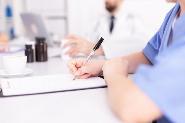 동료들과 회의하는 동안 파란색 유니폼을 입고 클립보드에 메모를 작성하는 의료 여성 개업의. 질병에 대해 동료들과 이야기하는 클리닉 전문 치료사, 의학 전문가.