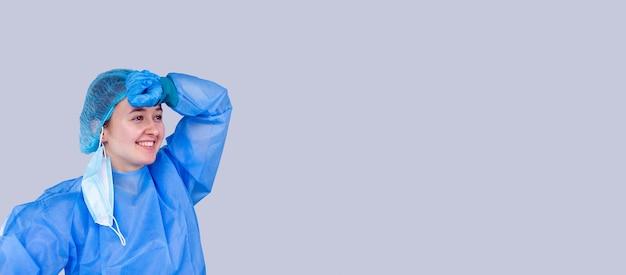 과로에 지쳤지만 웃고 있는 제복을 입은 의료 여성 노동자가 머리에 손을 얹고 있습니다...