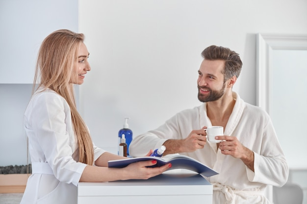 Medical worker consults with brochure and beauty treatments to patient. patient young man standing near the reception and holding tea.