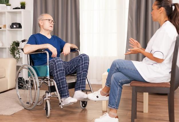 휠체어에 수석 남자에게 치료를 설명하는 의료 노동자.