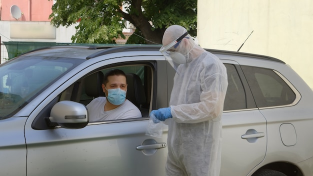 Medical worker in hazmat suit taking nose swab sample from driver through automobile window.