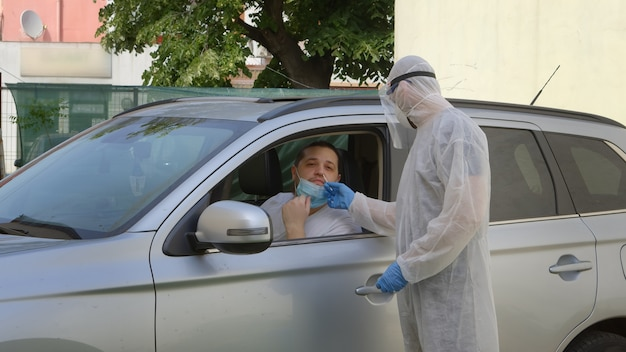 Medical worker in hazmat suit taking a swab sample from nose to a man in car seat