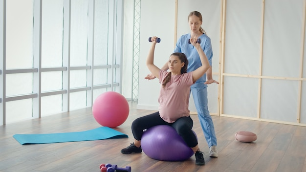 Medical worker helping pregnant woman to do ball exercises