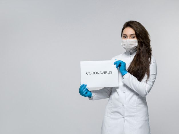 Medical worker holding piece of paper with coronavirus word