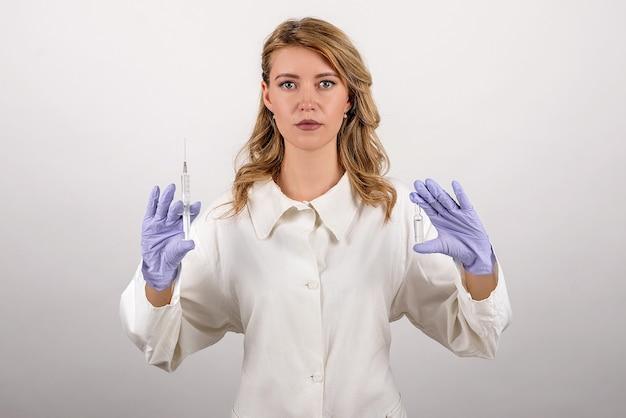 파란색 장갑에 의료 노동자는 그의 손에 주사기와 앰플을 보유