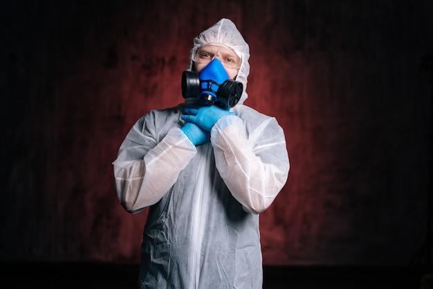 위험 물질 고글과 인공 호흡기를 착용한 의료 종사자가 손으로 자신을 질식시킵니다.