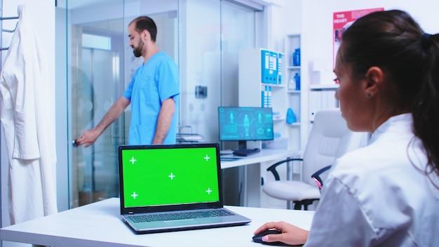 病院のキャビネットで緑色の画面とラップトップを使用して白衣を着た医療従事者。青い制服を着てガラスのドアを開ける看護師。メディックに展示されているクロマキー付きのノートを使用して制服を着たメディック