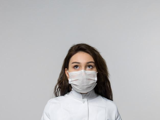 白い医療の制服と白い防護マスクで距離を見て医療従事者
