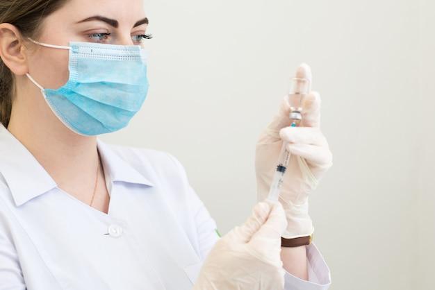 의료 노동자 간호사가 주사를 준비하는 그녀의 손에 주사기와 마스크와 장갑에 가까이