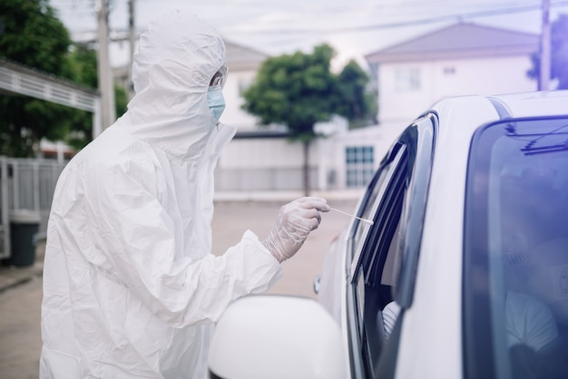 Medical worker in protective suit screening woman driver to sampling secretion to check for covid-19. check,taking nasal swab specimen sample from patient through car window,pcr diagnostic for corona