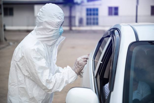 Medical worker in protective suit screening woman driver to sampling secretion to check for covid-19.