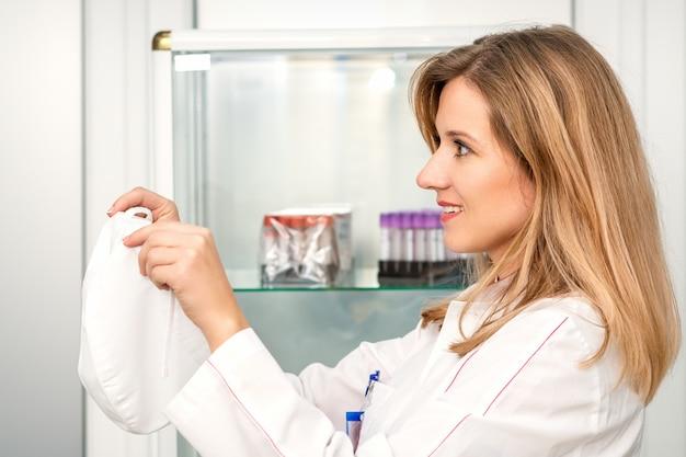 医療従事者は実験室で白い医療用ガウンを着て医療キャップを着用します