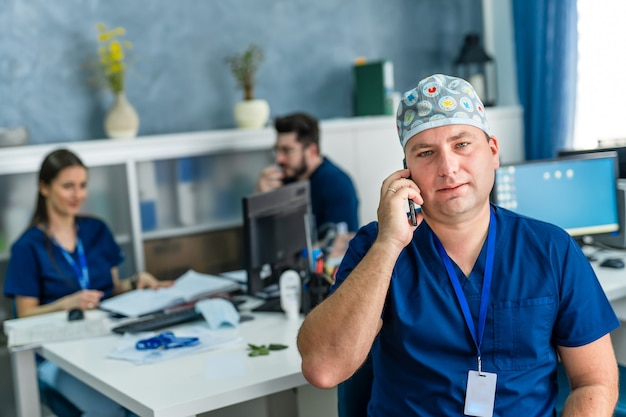 Medical worker sitting at desk. doctor in medical hat is speaking on mobile phone. looking at camera in office.