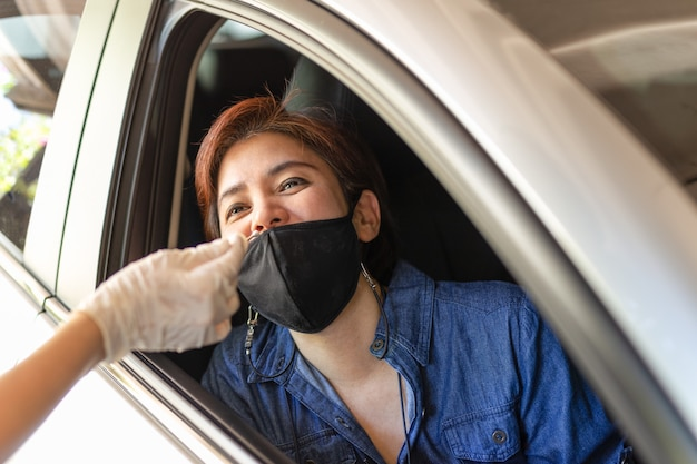 Medical worker taking nasal swab from woman in car to test for covid19 infection