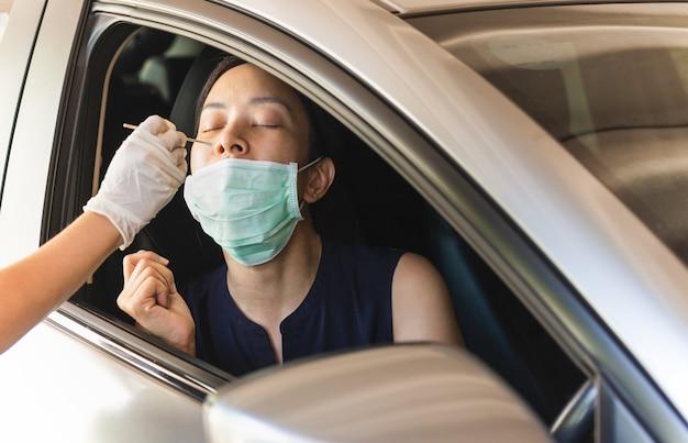 Covid19 감염 테스트를 위해 차에 탄 여성의 비강 면봉을 채취하는 의료 종사자